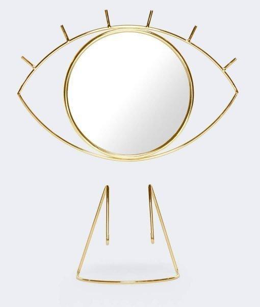Espejo de mesa elegante con una base dorada y desmontable para un fácil momento de maquillaje.Tiene la forma de un ojo gráfico.