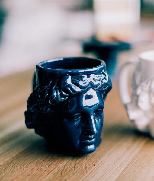 Taza de cerámica blanca con forma de dios grecorromano, Apolo.